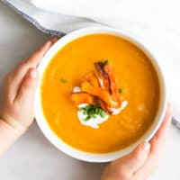Child Grabbing Bowl of Carrot and Orange Soup