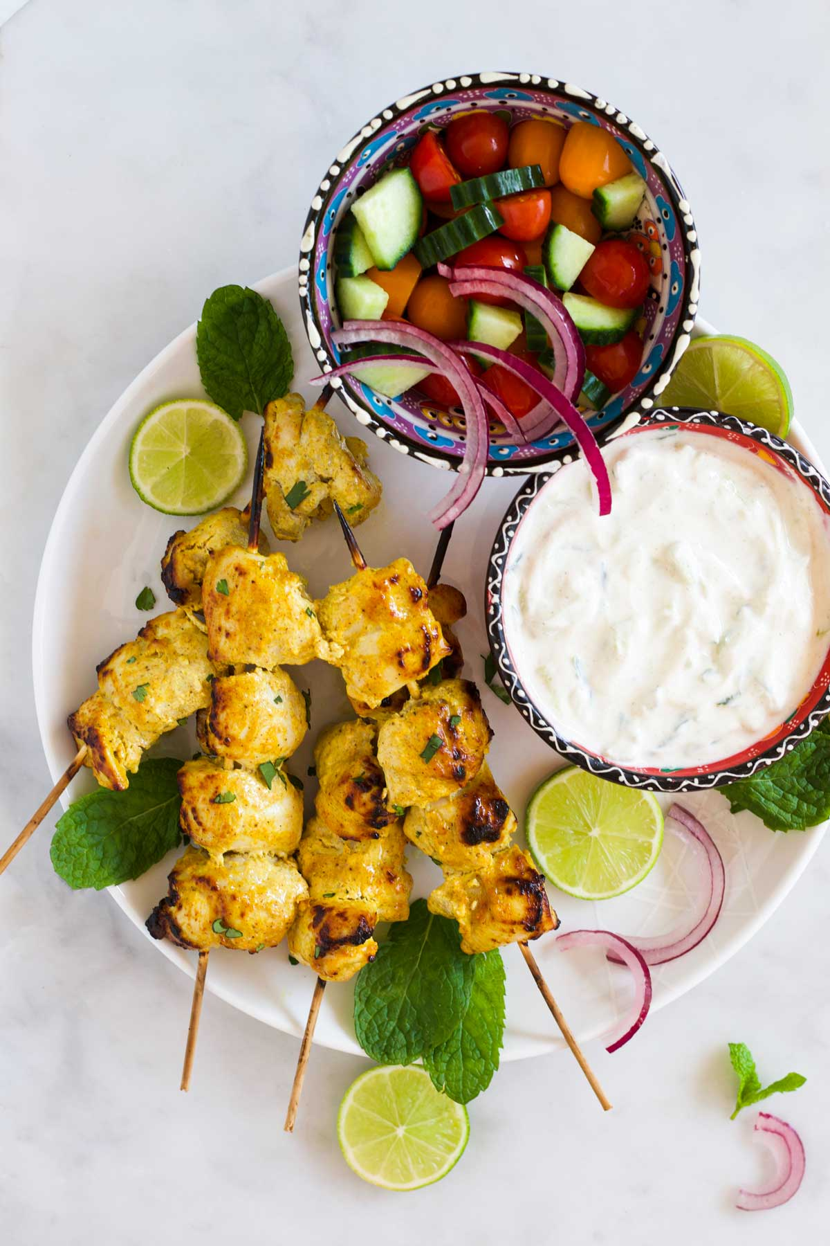 Chicken Tikka Kebabs on Plate Along with Mint Leaves and Lime Wedges with Bowl of Salad, Bowl and Raita on Side.