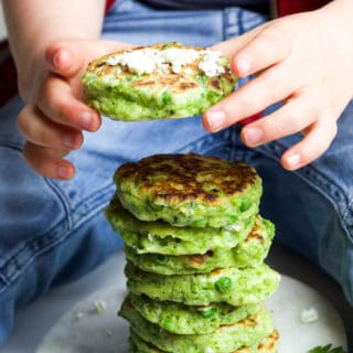 Child Grabbing a Pea Fritter from a Stack