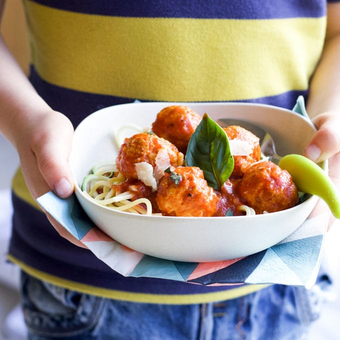 Child Holding Bowl of Turkey Meatballs in Tomato Sauce