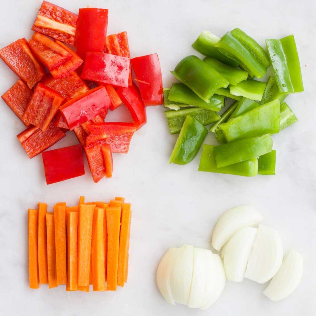 Top Down View of Red and Green Pepper Cut in Chunks, Carrots Cut into Stick and Onion Cut into Wedges