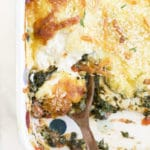 Close Up of Baked Chicken Florentine in Baking Dish with Portion Removed