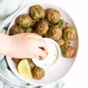 Child Dipping Spiced Meatball in Mint Yogurt Sauce