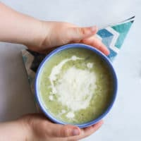 Child Grabbing Bowl of Courgette Soup (Zucchini)