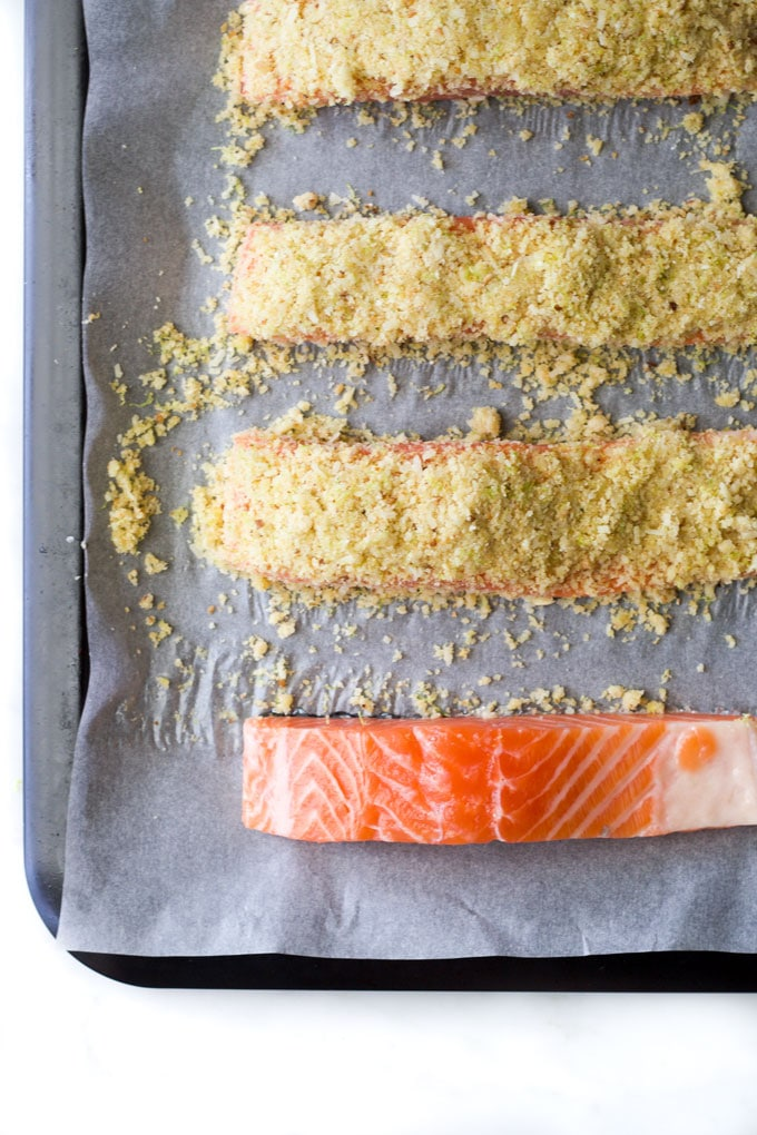raw salmon fillets on baking tray before and after parmesan crust pot on top