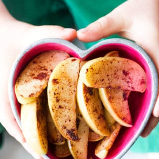 Child Holding a Bowl of Sautéed Apple and Cinnamon Wedges.