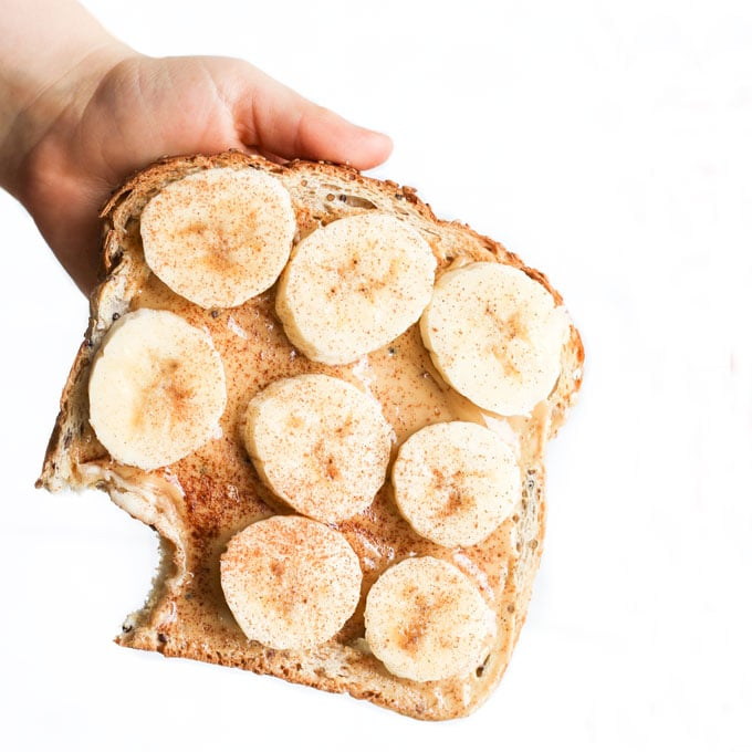 Child Holding Toast Topped with Nut Butter and Banana