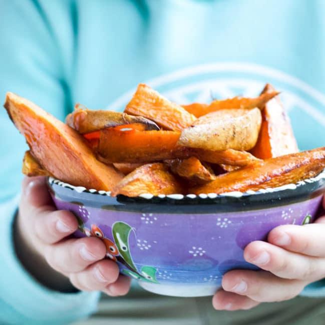 Child Holding Bowl of Sweet Potato Wedges