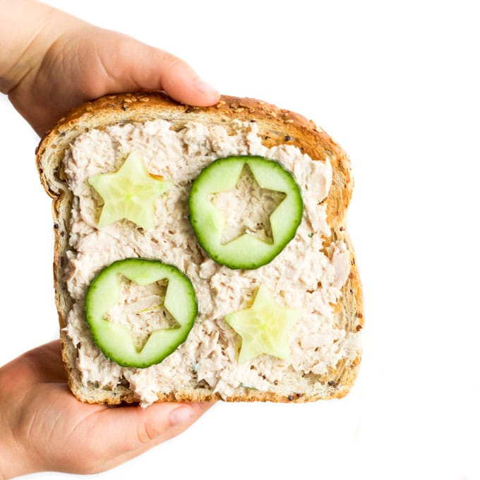 Child Holding Slice of Toast with a Toast Topping of Tuna and Cucumber