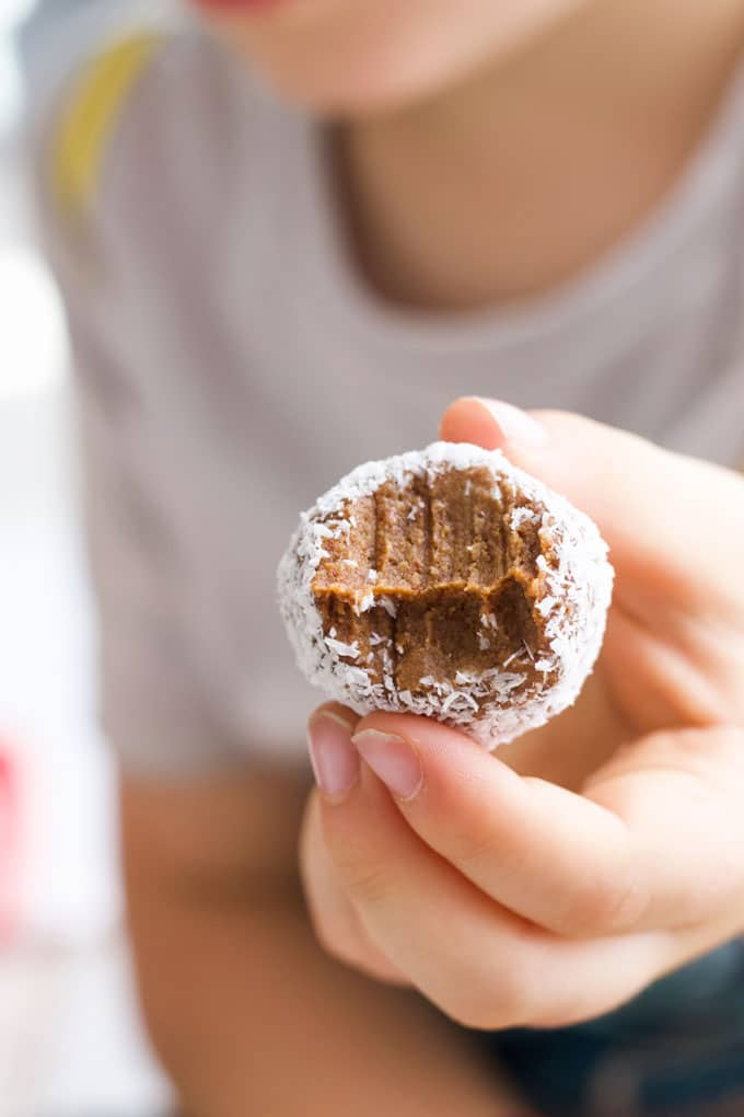Child Holding Sweet Potato Truffle with Bite Out of It