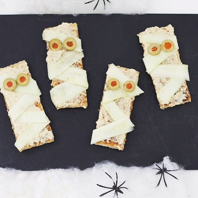 Mummy toast is a great healthy halloween snack for kids. Hummus on toast with courgette ribbons and sliced olives. Tasty and fun!