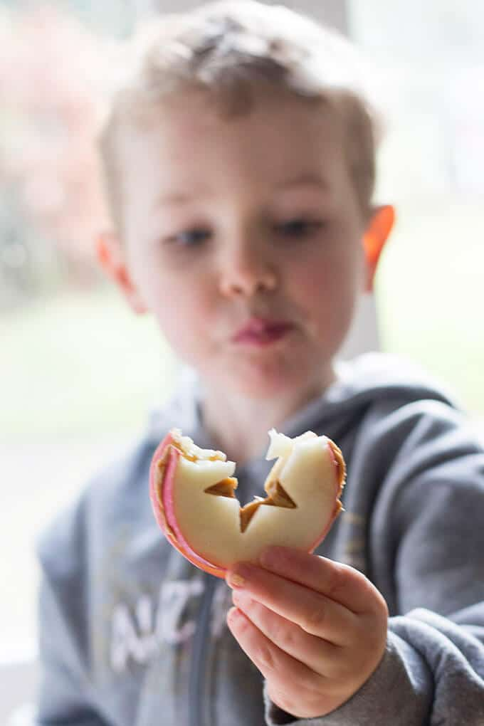 Child Eating Apple and Peanut Butter Sandwich