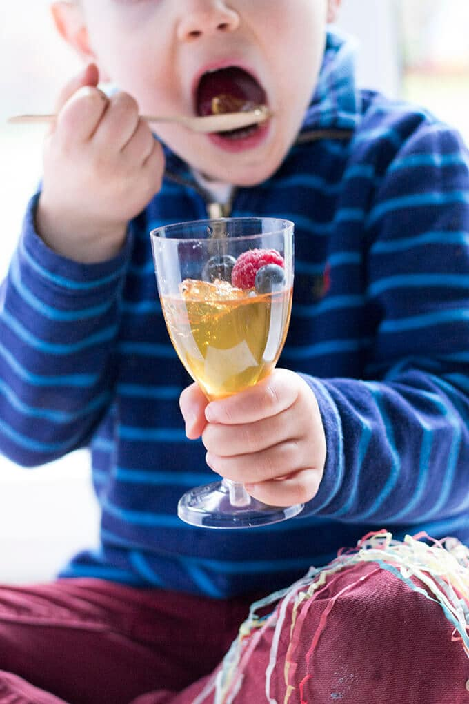 Fruit juice jelly served in a champagne glass and topped with fresh fruit