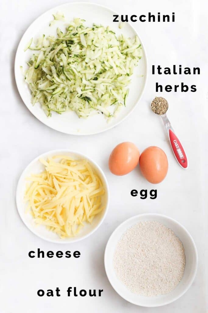 Flat Lay Shot of Ingredients Needed to Make Zucchini Bites (Grated Zucchini, Grated Cheese, Egg Oat Flour, Italian Herbs)