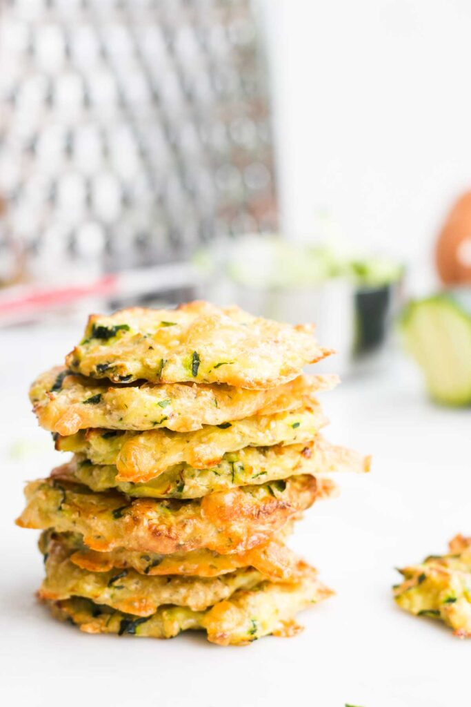 Side Shot of a Stack of Zucchini Bites with Grater and Ingredients in Background