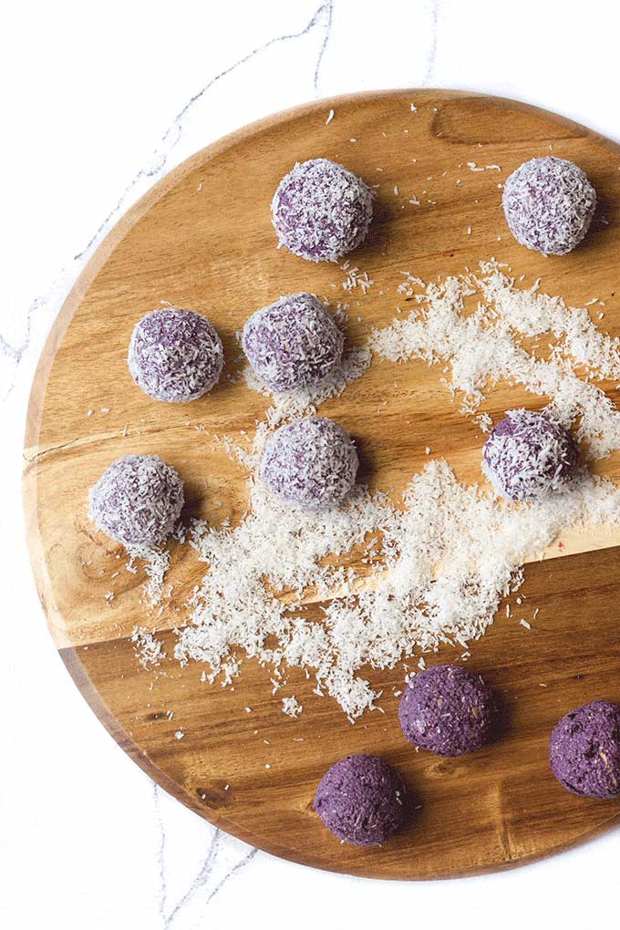 Top Down Shot of Blueberry Breakfast Balls on Wooden Board. Some Coated in Coconut, Others Left Uncoated.