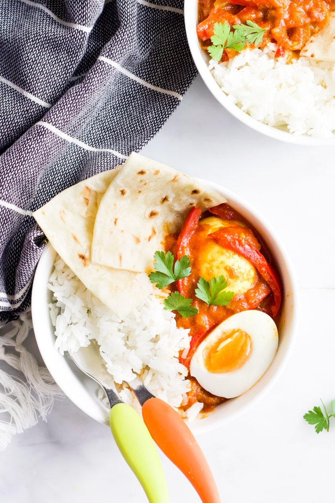 Bowl of Egg Curry Served with Rice and Roti Bread