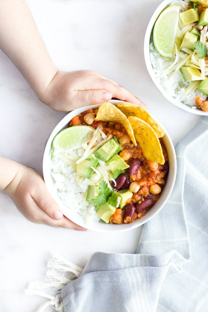 Child Grabbing Bowl of Vegetarian Chilli Topped with Cheese , Avocado and Corn Chips