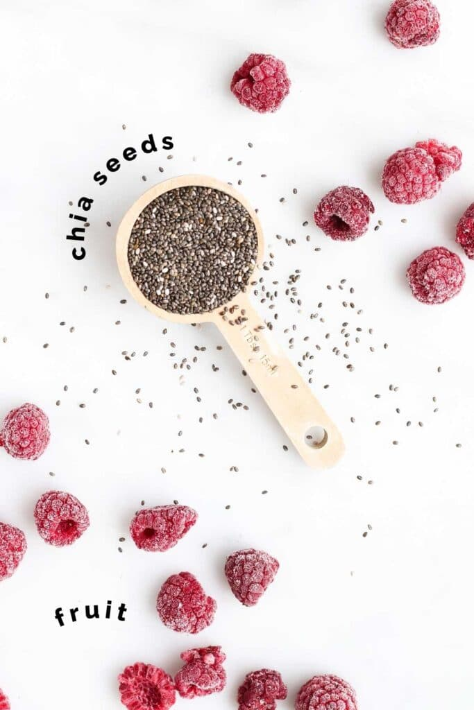 Top Down View of a Tbsp of Chia Seeds and Frozen Raspberries Scattered