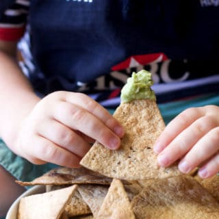 Child Holding Baked Tortilla Chip Dipped in Guacamole