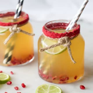 Mocktail served in glass jar with pomegranate and lime