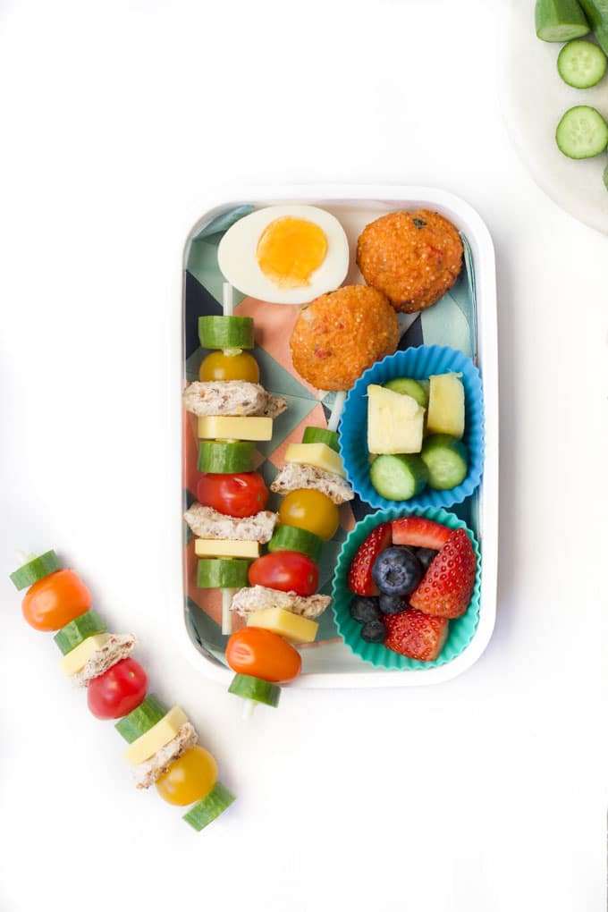 Healthy Lunchbox filled with Sandwich Kebabs, Egg, Quinoa Balls, Vegetables and Fruit