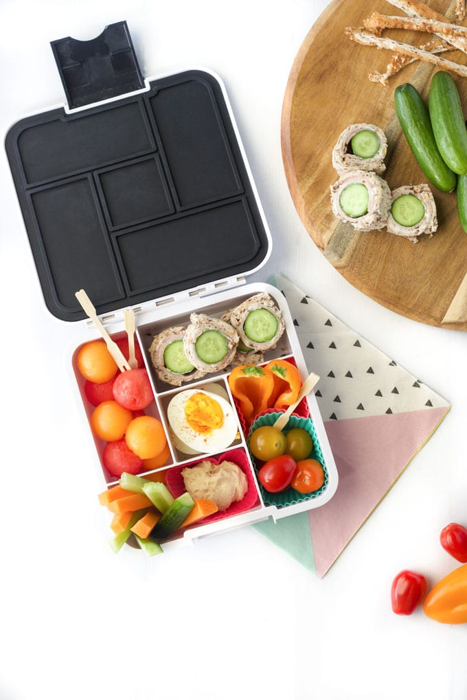 Healthy Lunchbox Filled with Quke Sandwich Sushi, Melon Balls, Egg, Vegetables and Dip
