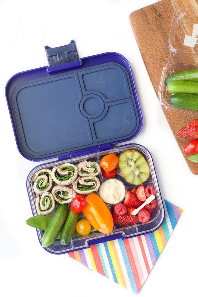 Lunchbox with Sandwich Scroll, Qukes, Mini Capsicum, Tomatoes, Kiwi , Berries and a Dip