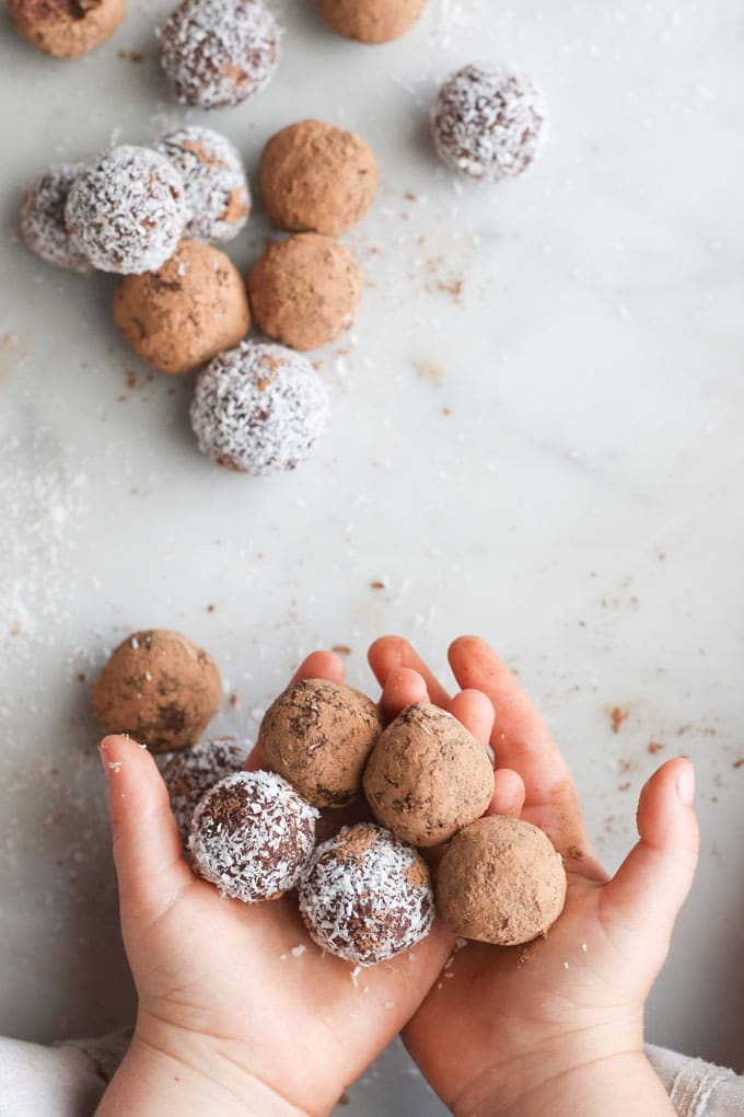 Child holding cherry bliss balls covered in cocao and coconut