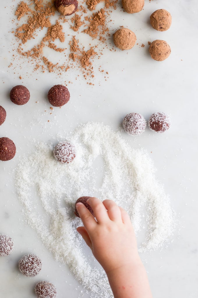 child rolling bliss balls in coconut