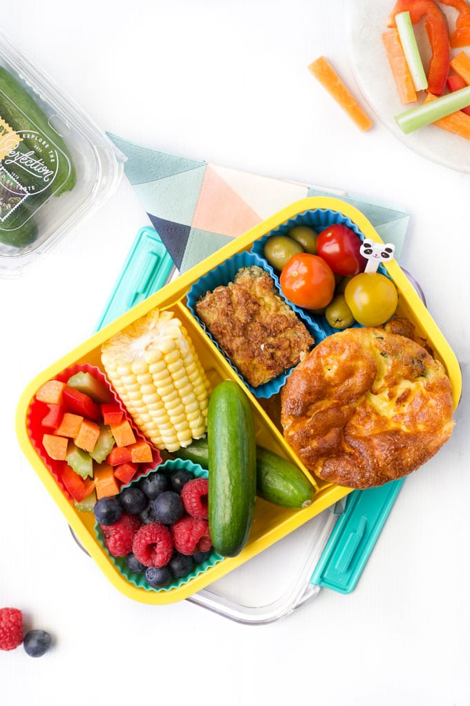 Healthy Lunchbox filled with Chopped Vegetables, Corn on the Cob, Qukes, Crustless Quiche, Oat Slice and Tomatoes
