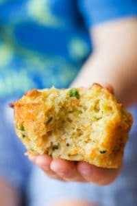 Child Holding Savoury Muffin with Bite Out of it.