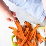 Child Grabbing Roasted Carrot Stick from Bowl