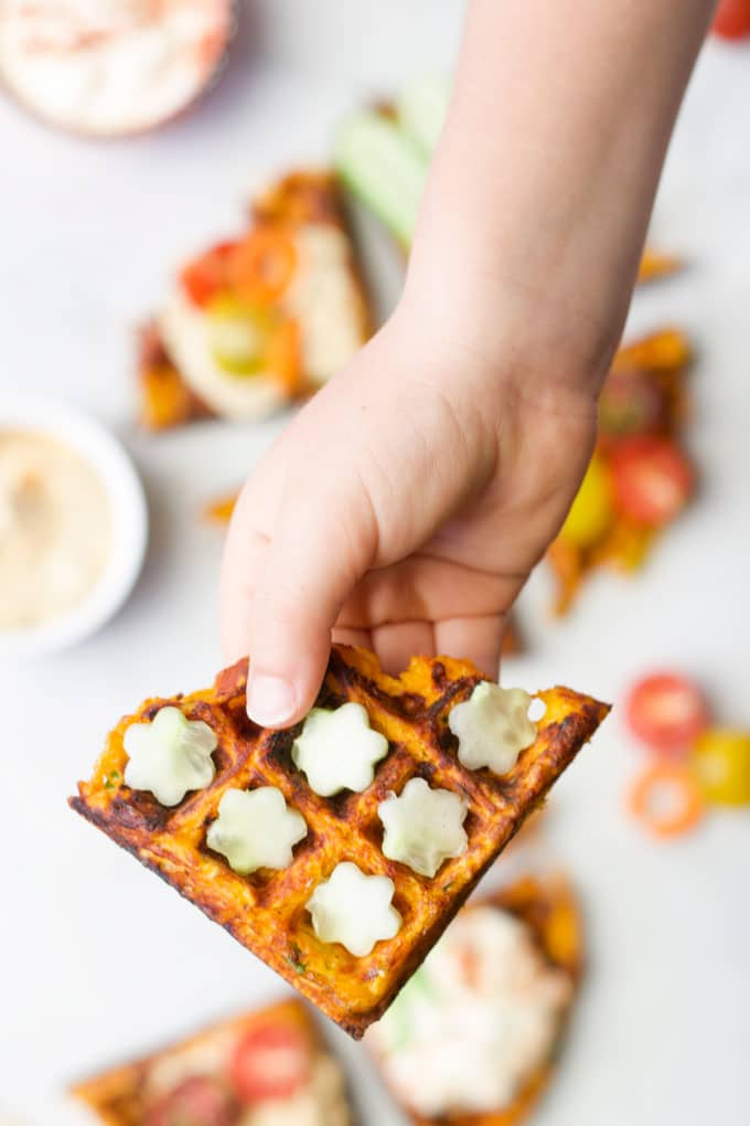 Child's Hand Holding Savoury Waffle with Cucumber Flowers Topping