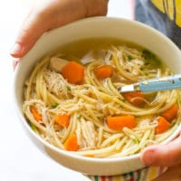Child Holding Bowl of Slow Cooker Chicken Noodle Soup