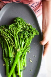 Child holding Plate of Sautéed Broccolini topped with Lemon Zest