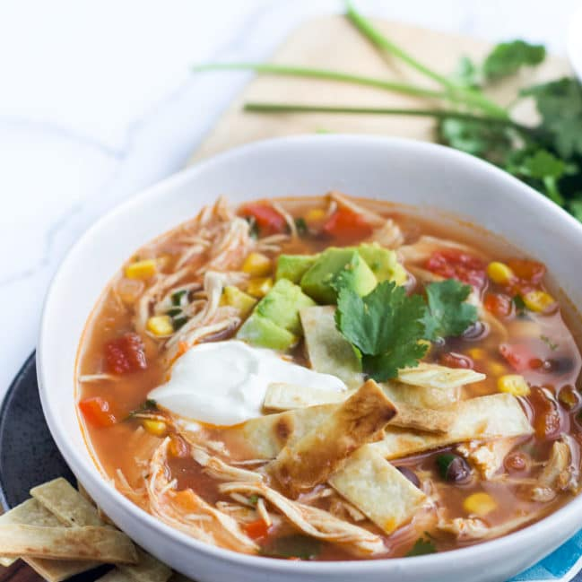 Bowl of Slow Cooker Chicken Tortilla Soup Topped with Avocado and Yoghurt
