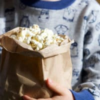 Child Holding Brown Bag of Popcorn