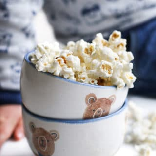 Homemade Popcorn in Bowl with Child Sitting in Background