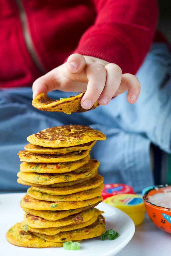 Child Grabbing Chickpea Pancake from a Stack