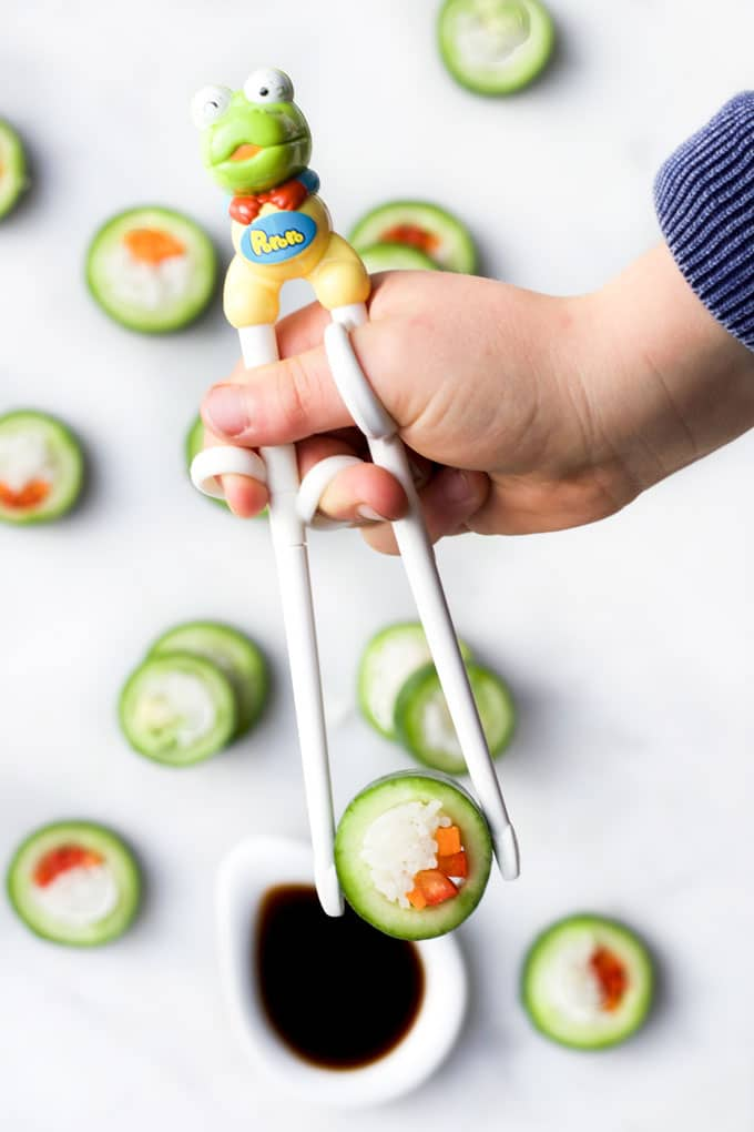 Child's Hand Picking Up Cucumber Sushi with Chop Sticks