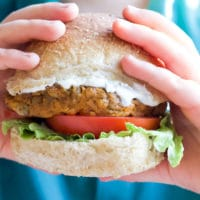 Child Holding Lentil Burger in Bun