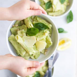 Child Holding Broccoli Pesto Pasta in Bowl