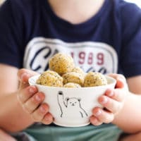 Child Holding Bowl of Apricot Balls