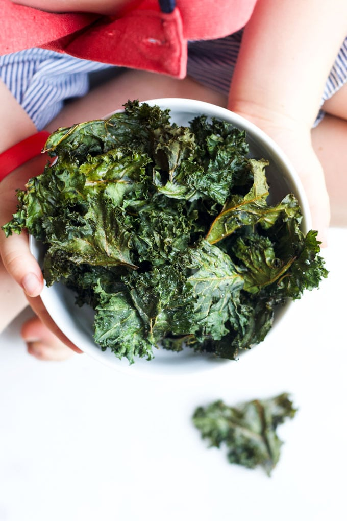 Child Holding a Bowl of Baked Kale Chips