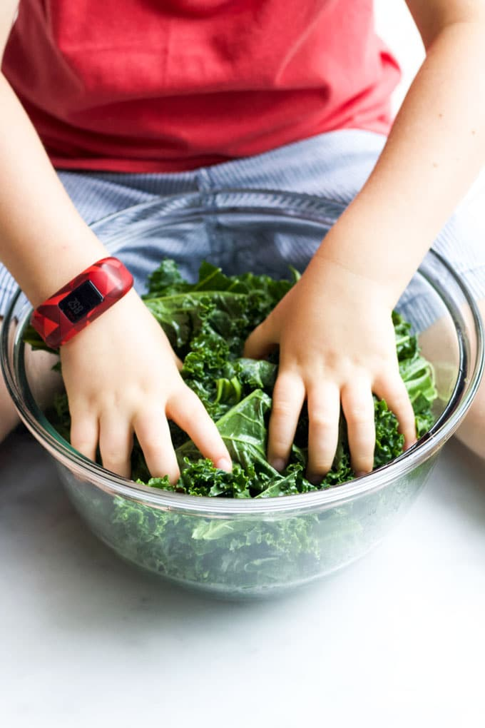 Child Massaging Kale in Bowl with Olive Oil.