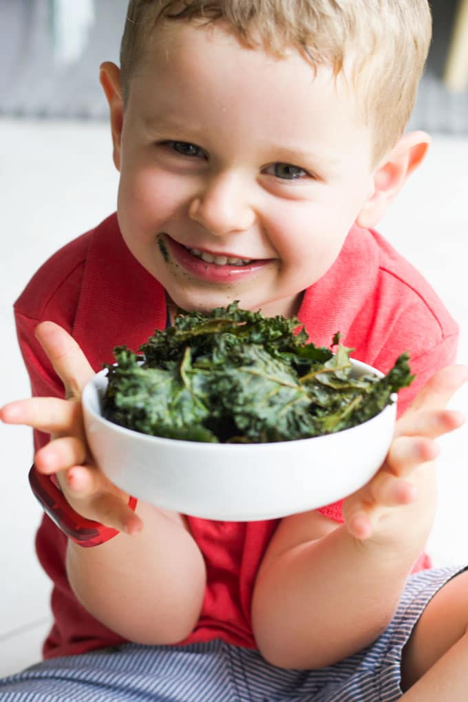 Child Smiling Holding a Bowl of Baked Kale Chips