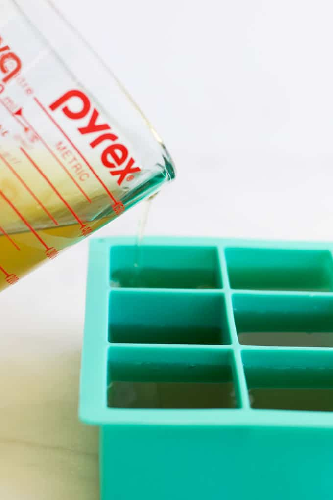Pouring Vegetable Stock into Ice Cube Tray for Freezing