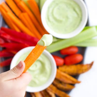 Child Dipping Carrot into Avocado Dip