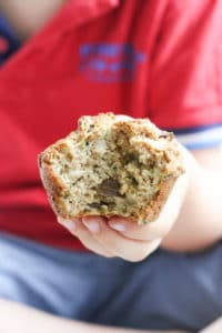 Child Holding a Zucchini Muffin with Bite Out